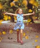 Den gladlynta lilla flickan i en färgrik höst parkerar arkivbilder