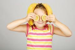 Den gladlynta lilla flickan med citronen och bananen poserar positivt in Royaltyfri Fotografi