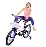 Den gladlynta lilla flickan på sportar cyklar på en vit bakgrund Royaltyfri Fotografi