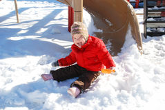 Den gladlynta lilla flickan sitter i snön på lekplatsen Royaltyfri Fotografi