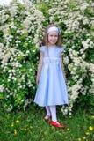 Den gladlynta lilla flickan står i buskarna av en hägg Arkivfoton