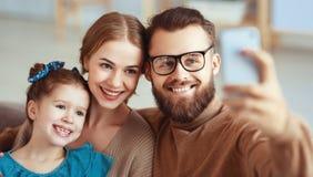 Den gladlynta lyckliga det familjmoderfadern och barnet tar selfies, tar bilder fotografering för bildbyråer