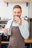 Den gladlynta manliga kaféarbetaren smakar gjord espresso royaltyfri foto