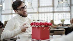 Den gladlynta mannen ger en stor ask mycket av blommor till hans fru, medan sitta i ett kafé arkivfilmer