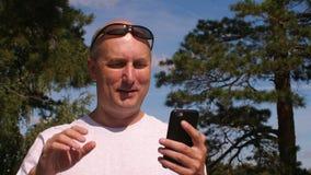 Den gladlynta mannen som använder smartphonen för den videopd pratstund- och vinkahanden i sommar, parkerar stock video