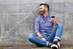 Den gladlynta mitt åldrades mansammanträde utanför med mobiltelefonen Arkivfoto
