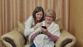 Den gladlynta modern och dottern tycker om den videopd appellen Se skärmen och att le för smartphone som hemma sitter på en stol arkivfilmer