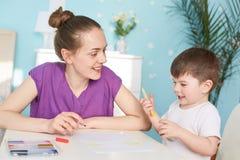 Den gladlynta mumen och sonen målar tillsammans, sitter på tabellen, som kreativitet, spenderar fri tid hemma, använder färgglade royaltyfria foton
