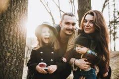 Den gladlynta och lyckliga familjen i höst parkerar arkivbild