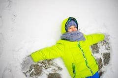 Den gladlynta pojken ligger på snö och gör vingar av en ängel Royaltyfri Bild