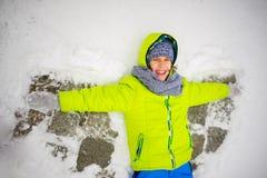 Den gladlynta pojken ligger på snö och gör vingar av en ängel Fotografering för Bildbyråer