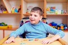 Den gladlynta pojken med handikapp på rehabiliteringmitten för ungar med sakkunniga behöver och att lösa det logiska pusslet Royaltyfria Foton