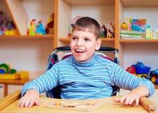 Den gladlynta pojken med handikapp på rehabiliteringmitten för ungar med sakkunniga behöver och att lösa det logiska pusslet Royaltyfri Bild