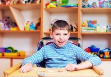 Den gladlynta pojken med handikapp på rehabiliteringmitten för ungar med sakkunniga behöver och att lösa det logiska pusslet Royaltyfri Foto
