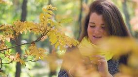 Den gladlynta rödhåriga unga kvinnan med fräknar på telefonen och läser meddelanden, medan gå i hösten, parkerar på a stock video