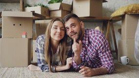 Den gladlynta skäggiga grabben ger tangent till hans flickvän och kysser henne som ligger på golv av den nya lägenheten Affektion arkivfilmer