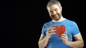 Den gladlynta skäggiga mannen i blå tshirt rymmer en röd hjärtaform Förälskelse singel, romans, datummärkning, förhållandebegrepp Royaltyfri Bild