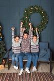 Den gladlynta skrikiga studsa familjen på soffan ut ur farsa- och siblingbarn som upp kastar deras händer i det nya året, dekorer royaltyfri fotografi