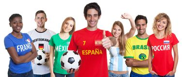 Den gladlynta spanska fotbollfanen med bifallgruppen av annan fläktar Arkivbilder
