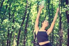 Den gladlynta sportive kvinnan med vattenflaskan parkerar in royaltyfri bild
