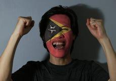 Den gladlynta ståenden av en man med flaggan av Östtimor målade på hans framsida på grå bakgrund Begreppet av sporten eller natio royaltyfria bilder