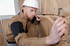 Den gladlynta stuckatörarbetaren på väggisolering arbetar inomhus fotografering för bildbyråer