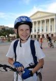 Den gladlynta tonåringen med cykeln nära den Tyumen dramateatern. Royaltyfri Fotografi