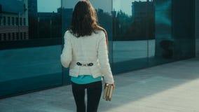 Den gladlynta unga brunettstudentflickan går i gatan med böcker i händer och leenden stock video