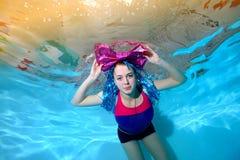 Den gladlynta unga flickan med den stora pilbågen på ditt huvud simmar i pölen som är undervattens- och ser kameran Stående den k Arkivfoto