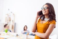Den gladlynta unga flickan meddelar på telefonen Fotografering för Bildbyråer