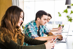 Den gladlynta unga gruppen av freelancers arbetar med glädje i modernt kontor Arkivbild