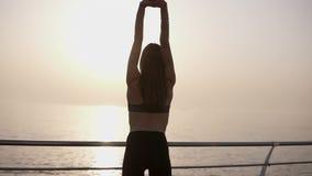Den gladlynta unga kvinnan öppnar armar till soluppgång på sjösidan Slankt och behagfullt, i damasker Sikt för tillbaka sida stock video