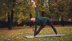 Den gladlynta unga kvinnan gör yoga som balanserar övningar under individuell övning i stad, parkerar anseende på mattt och lager videofilmer