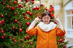 Den gladlynta unga kvinnan som tycker om jul, kryddar i Paris Royaltyfria Foton