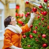 Den gladlynta unga kvinnan som tycker om jul, kryddar i Paris Arkivbilder