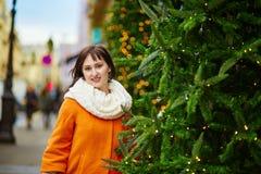 Den gladlynta unga kvinnan som tycker om jul, kryddar i Paris Royaltyfri Foto