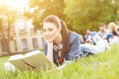 Den gladlynta unga kvinnan studerar i universitetsområde Royaltyfria Bilder