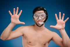 den gladlynta unga mannen i snorkel och dykning maskerar att göra en gest med händer och att se kameran Royaltyfri Fotografi