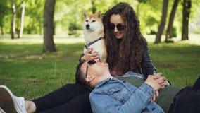 Den gladlynta unga mannen ligger på gräset i parkera med hans huvud på hans ben för fru` s, medan den attraktiva le kvinnan är lager videofilmer