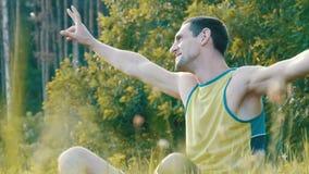 Den gladlynta unga mannen sitter på ett grönt gräs i sommar och ler stock video