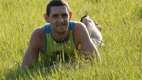 Den gladlynta unga mannen sitter på ett grönt gräs i sommar och ler lager videofilmer