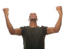 Den gladlynta unga mannen som ropar med armar, lyftte i framgång Royaltyfri Fotografi