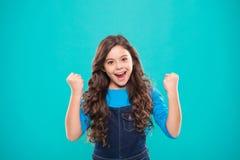 Den gladlynta ungen firar seger Le för lockigt hår för gulligt barn för flicka långt lyckligt Barnpsykologi och utveckling Lyckli royaltyfri bild