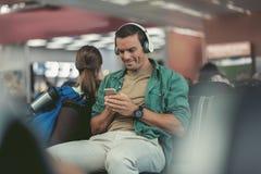 Den gladlynta vuxna handelsresanden använder smartphonen arkivbild