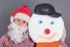 Den gladlynta vuxna kvinnan med ett Santa Claus skägg omfamnar en snögubbe arkivbild