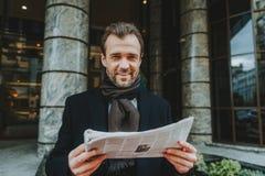 Den gladlynta vuxna mannen läser den utomhus- tidningen royaltyfri bild