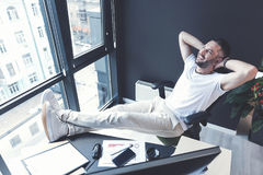 Den gladlynta vuxna mannen vilar i regeringsställning royaltyfri fotografi
