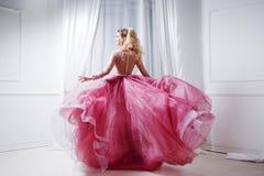 Den glamorösa damen i en chic rosa färg klär med ett drev Studiostående i den vita inre, baksidasikt arkivbilder