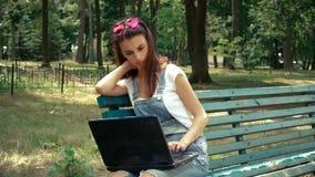 Den glamorösa unga flickan med exponeringsglas sitter i parkera öppnar bärbara datorn stock video