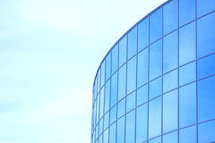 Den glass fasaden av en skyskrapa med en spegelreflexion av himmelfönster Arkivfoto